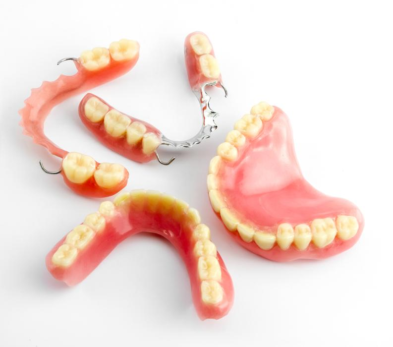 Sets of full and partial dentures at Lexington dentist office