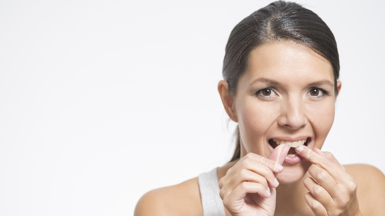 Woman Flossing | Dental Cleanings in Lexington